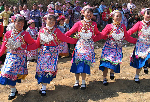 Minority girls dressed in colorful ethnic clothes in Anshun are singing and dancing happily.