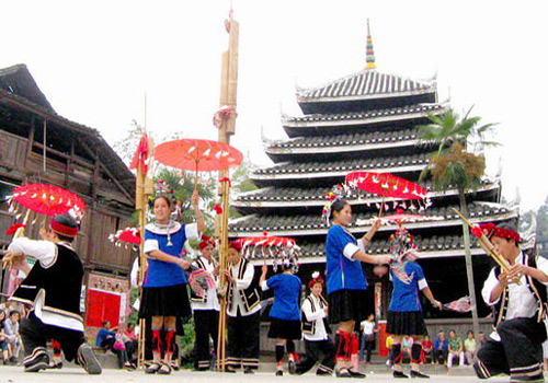 Dong people is celebrating their festival by a drum tower.