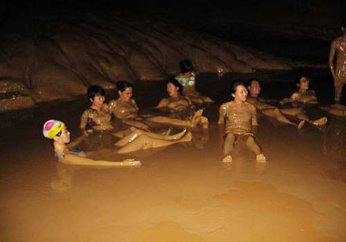 Tourists are enjoying the mud bath inside the Buddha Water Cave.