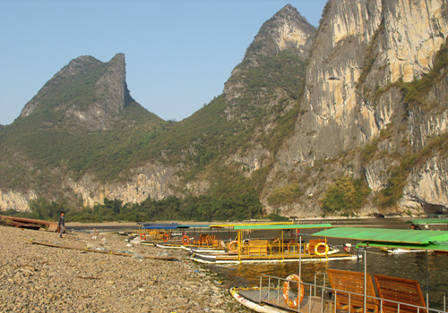 Small bamboo rafts are berthing by the Li River.Some tourist prefer to have a more leisurely Li River cruise by them.