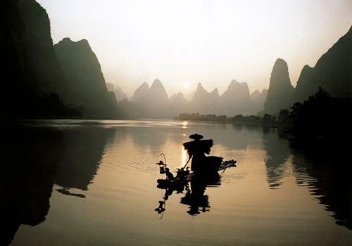 An old man wearing straw cloak is fishing with his cormorants at dusk on Li River.