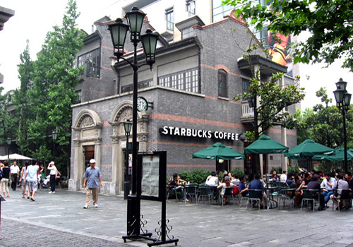 People spend their leisure time at the Starbucks Coffee in Shanghai Xintiandi.