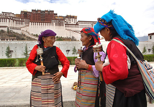 Three senior Tibetan female Buddhists are talking in front of the Potala Palace.