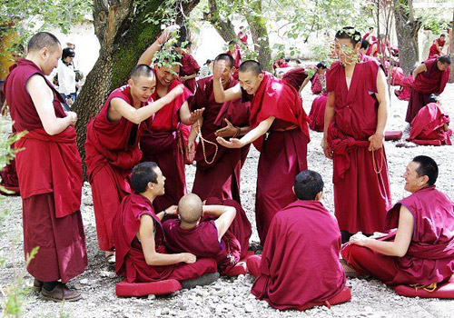 Monks of Sera Monastery are debating Buddhist sutra happily.