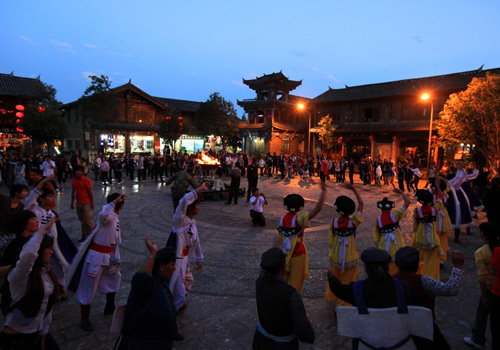 Tourists are dancing with local ethnic minotiry of Shuhe Ancient Town around the bonfire.