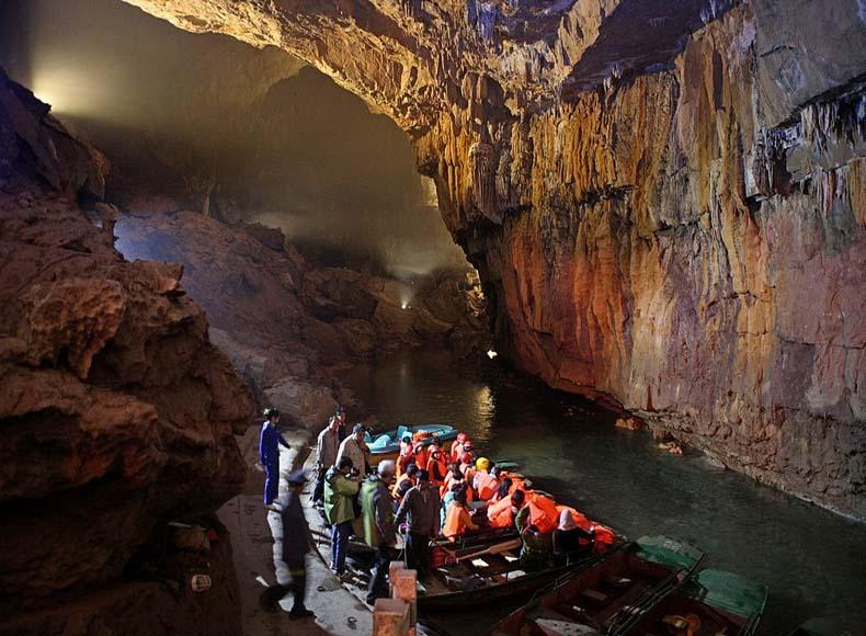Tourists can take a boat trip on a subterranean river in the Silver Cave Scenic Area, China
