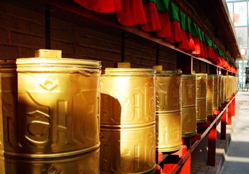 Walk around prayer wheels clockwise in Tibetan areas.